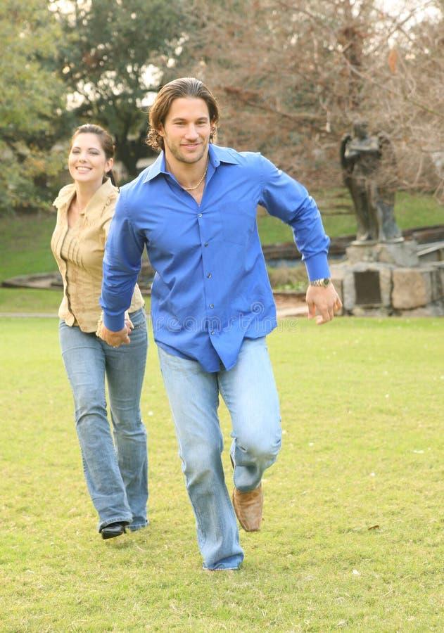 夫妇愉快的公园运行的年轻人 免版税图库摄影