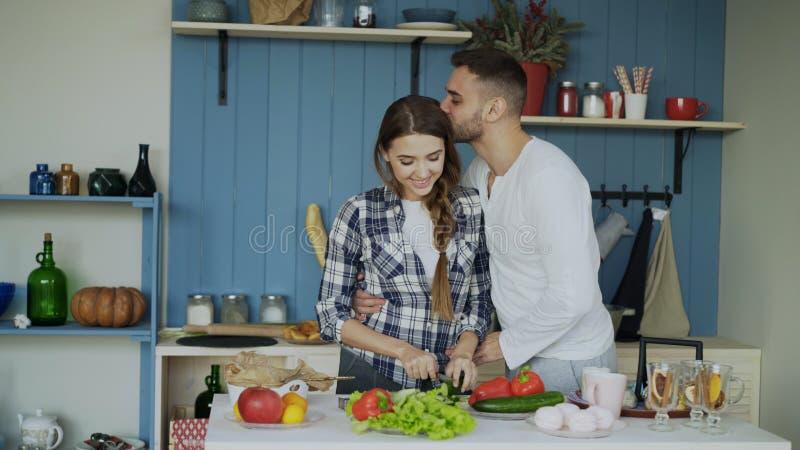 夫妇愉快的厨房年轻人 烹调可爱的妇女,当她的亲吻她的男朋友早晨时 免版税图库摄影