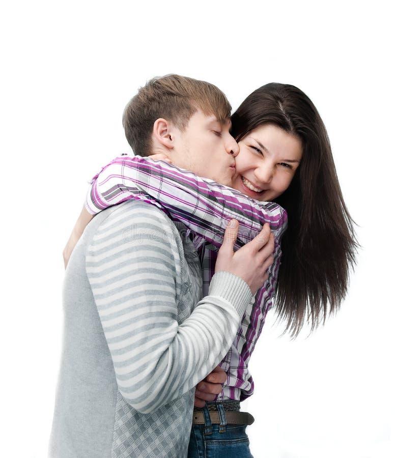 夫妇愉快的查出的亲吻的空白年轻人 免版税库存照片