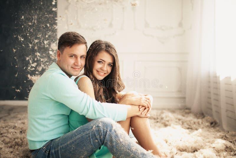 夫妇愉快的爱年轻人 在地板上的许多羽毛 图库摄影