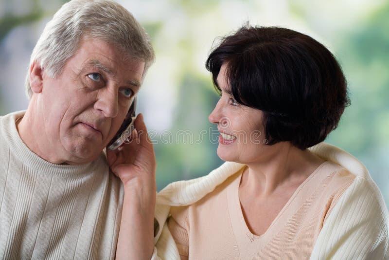 夫妇愉快的移动老电话 免版税库存图片
