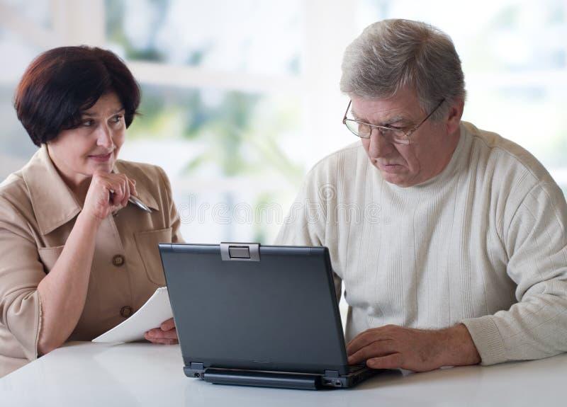 夫妇愉快的膝上型计算机成熟工作 免版税库存照片