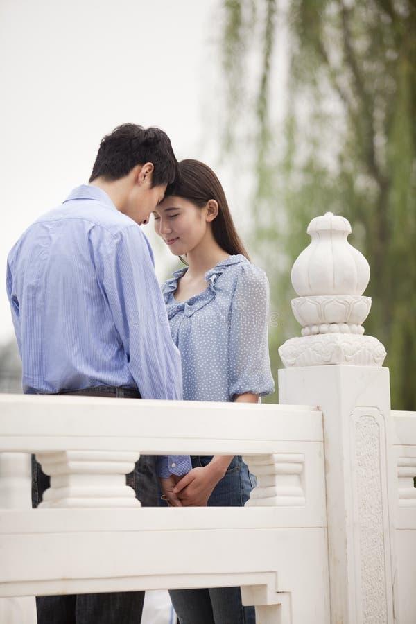 年轻夫妇感人的前额和举行手在桥梁 图库摄影