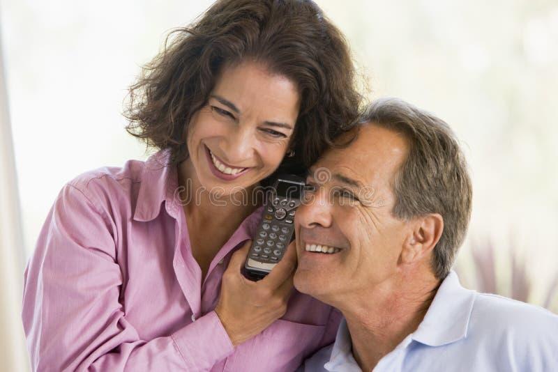 夫妇户内微笑的电话使用 免版税库存图片