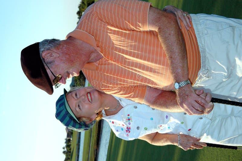 夫妇打高尔夫球前辈 图库摄影