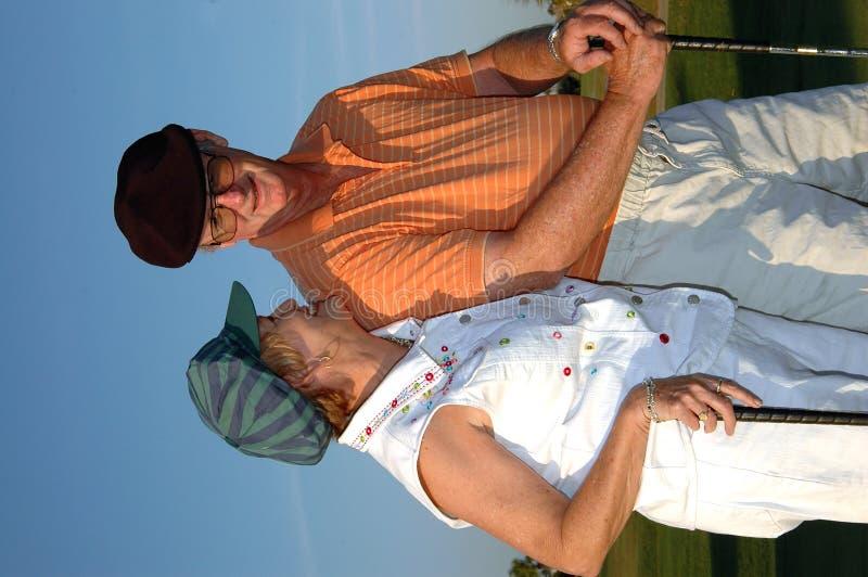夫妇打高尔夫球前辈 免版税库存照片
