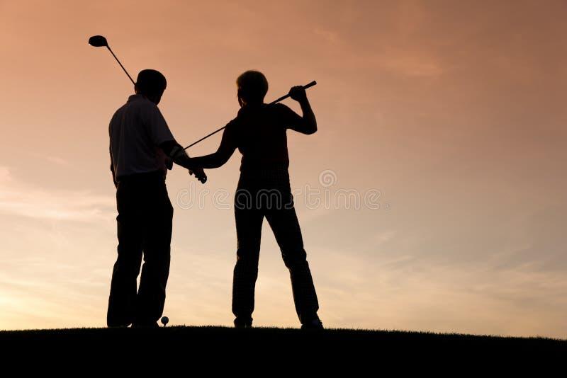 夫妇打高尔夫球成熟使用的日落 库存照片