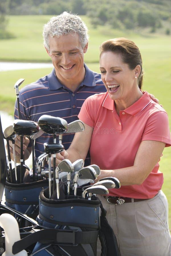 夫妇打高尔夫球演奏微笑 免版税库存图片