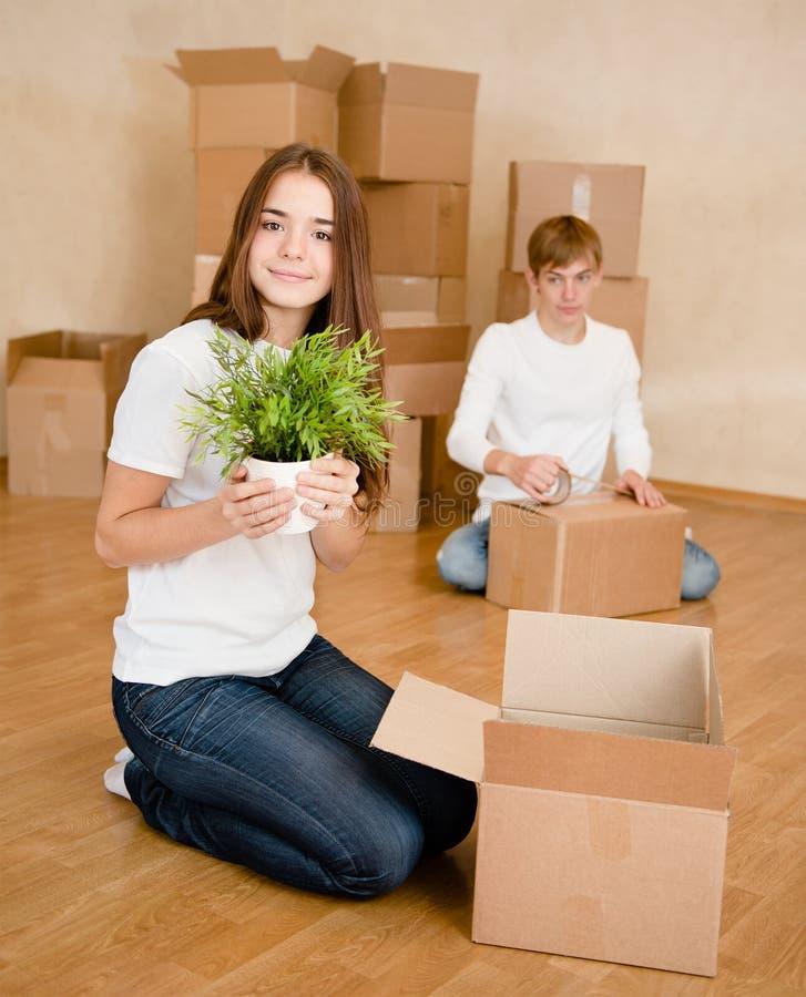 年轻夫妇投入在纸板箱的事搬入的一个新房 免版税库存图片