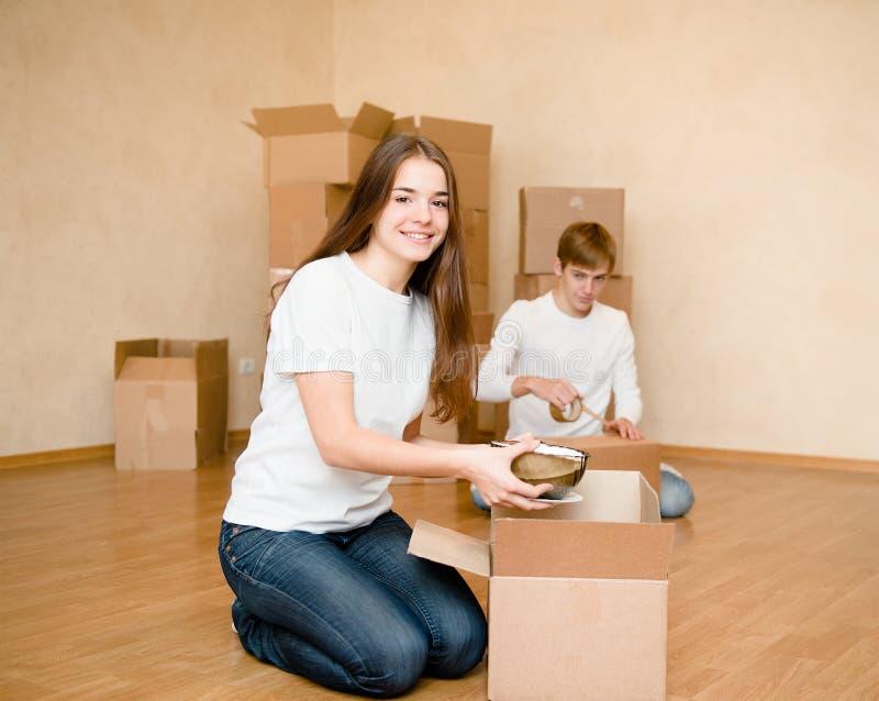 年轻夫妇投入在纸板箱的事搬入的一个新的家 库存照片