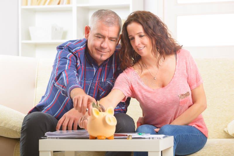 夫妇挽救金钱 免版税图库摄影