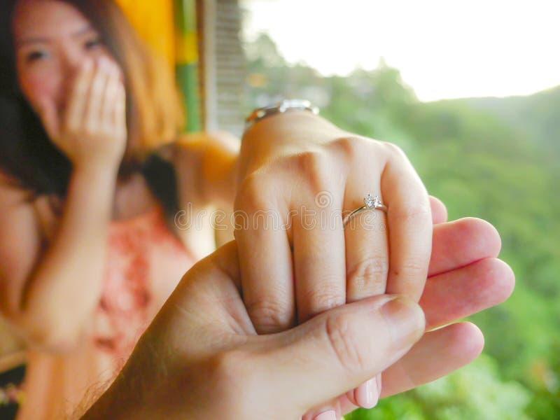 夫妇握有金刚石定婚戒指的手人的关闭愉快的未婚夫手在她的手指在婚姻的提案以后在热带 免版税库存图片