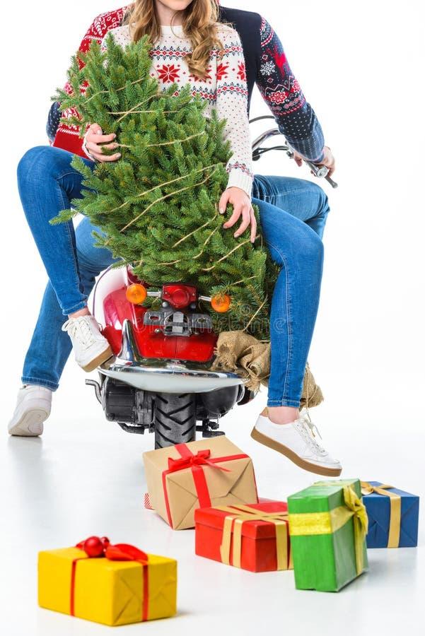 夫妇播种的看法在圣诞老人帽子的有乘坐红色滑行车的礼物盒的, 免版税库存照片