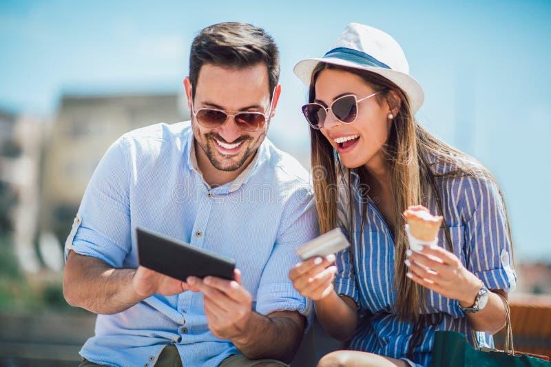 夫妇支付在与信用卡的线的和在街道上的数字片剂 免版税库存图片
