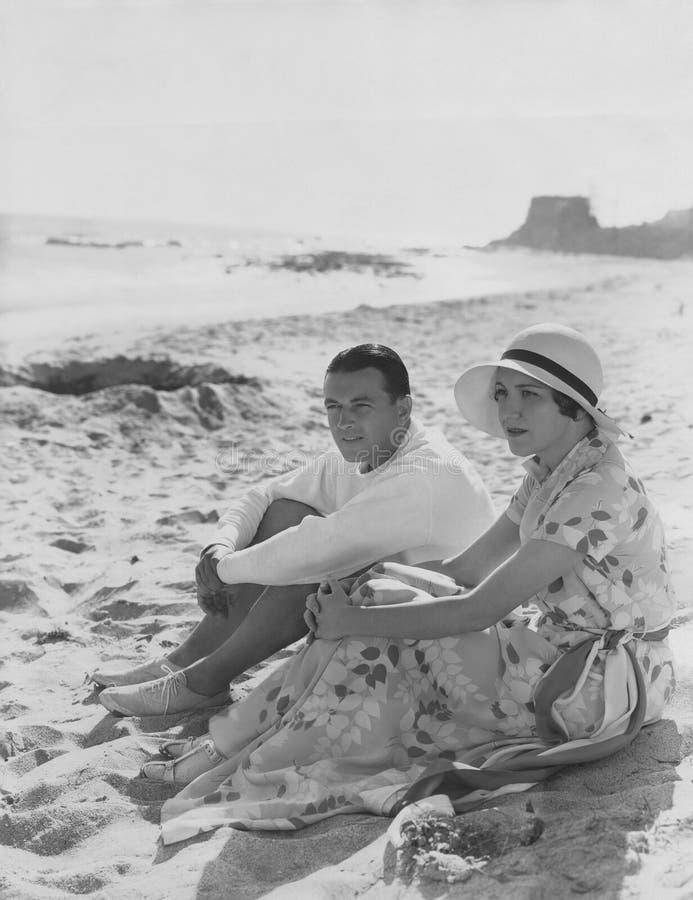 夫妇放松在海滩 免版税库存图片