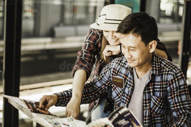 夫妇旅客,在平台i读地图计划旅行 图库摄影