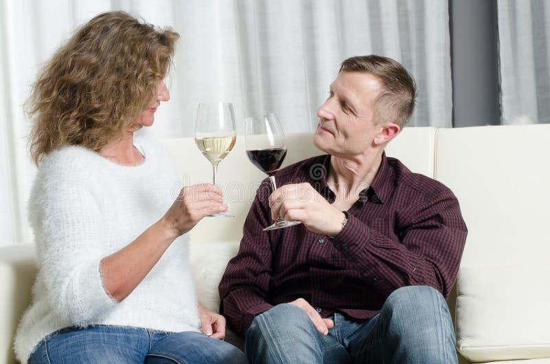 夫妇是在长沙发的品酒 免版税库存照片