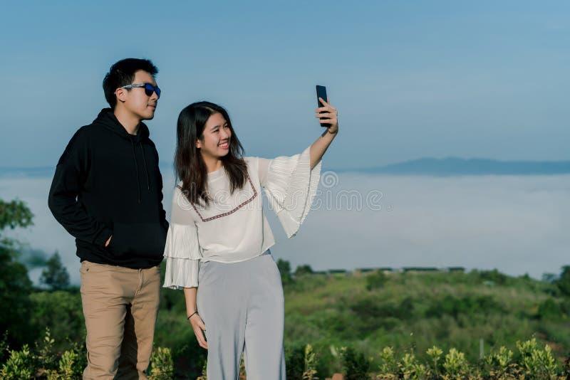 夫妇是约会的恋人由智能手机一起采取selfies有小山的顶视图在backgroud的 一个亚洲人 免版税库存照片