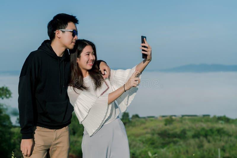 夫妇是约会的恋人由智能手机一起采取selfies有小山的顶视图在backgroud的 一亚洲adolesc 免版税图库摄影