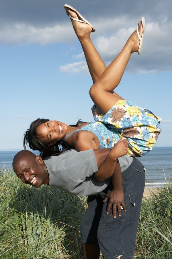 夫妇有沙丘的乐趣沙子年轻人 免版税库存图片