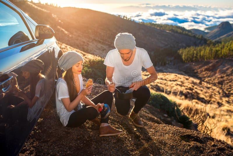 夫妇有野餐在汽车附近 免版税库存图片