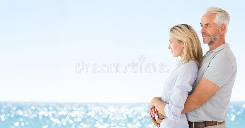 夫妇朝左边看反对模糊的海滩 免版税库存照片