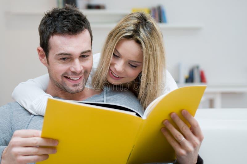 夫妇杂志读取年轻人 免版税图库摄影
