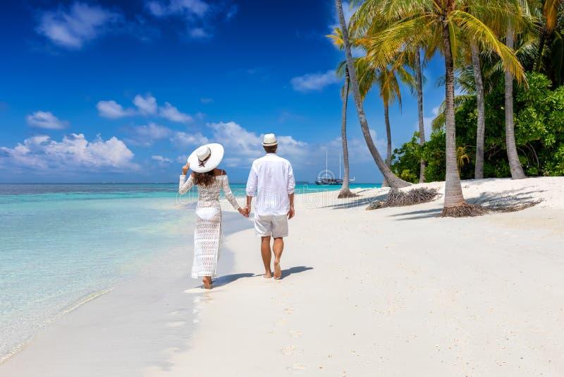 夫妇步行沿着向下一个热带海滩在马尔代夫海岛 免版税库存图片
