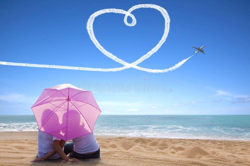 年轻夫妇浪漫亲吻在与伞的海滩 免版税库存图片