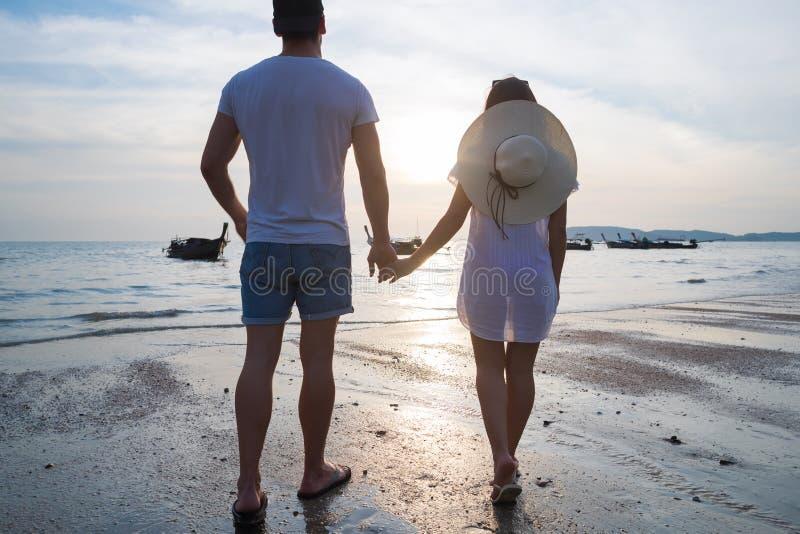 夫妇海滩暑假,举行手日落年轻人女孩后面背面图的人妇女 免版税库存图片