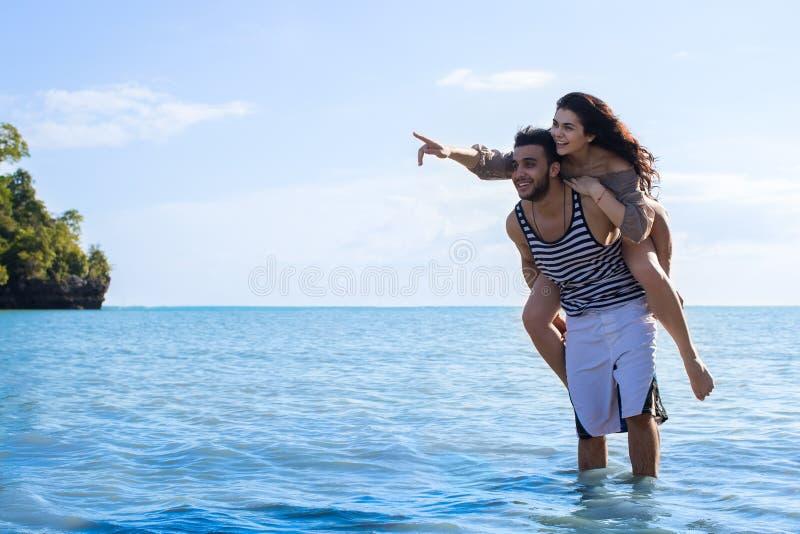 夫妇海滩暑假,人运载妇女点手指复制空间美好的年轻愉快的男人和妇女微笑 免版税库存图片
