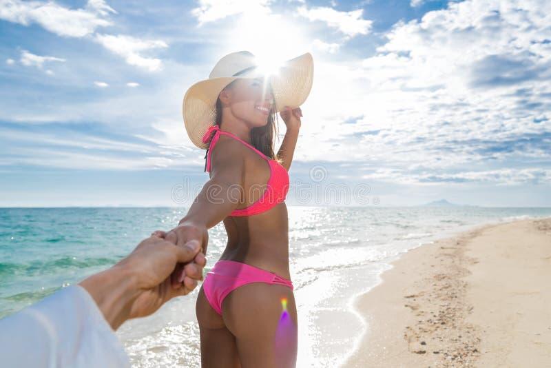 年轻夫妇海滩暑假,女孩举行人手愉快的微笑海边大海 免版税库存图片
