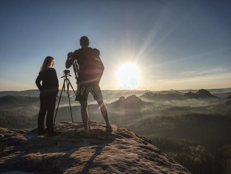 夫妇游人拍照片对小山和天空背景  库存例证