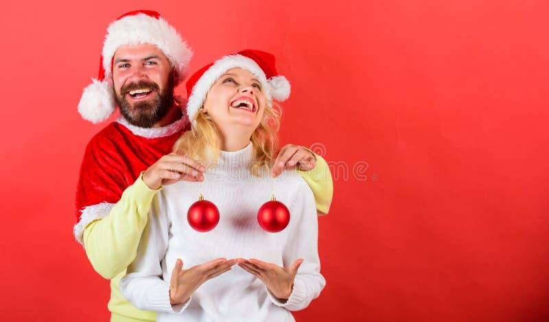 夫妇激动的举行圣诞节球 圣诞节奇迹概念 成熟在整容手术白人妇女 人圣诞老人帽子举行球圣诞节 免版税库存图片