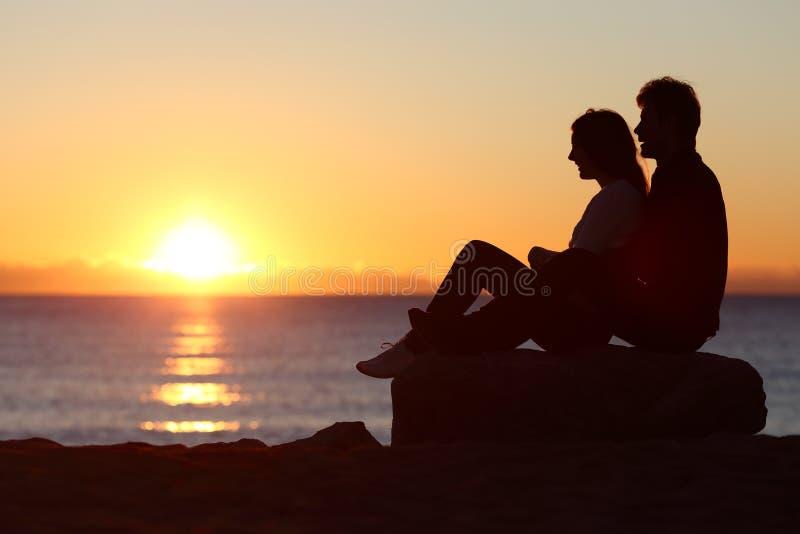 夫妇现出轮廓坐的观看的太阳在日落 图库摄影