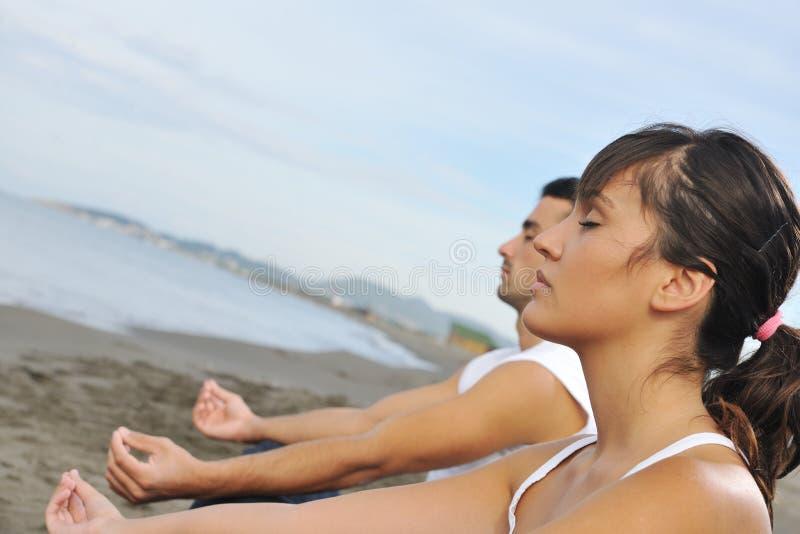 夫妇瑜伽海滩 库存照片