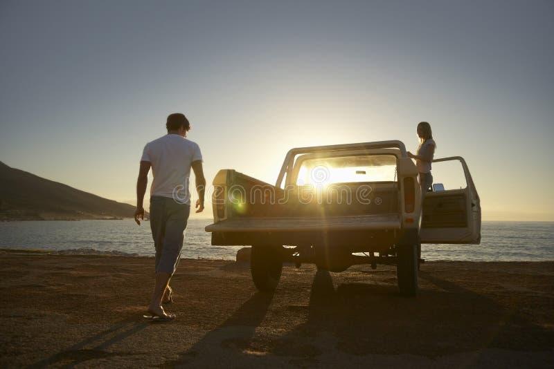 夫妇用在海滩停放的轻型货车 免版税图库摄影