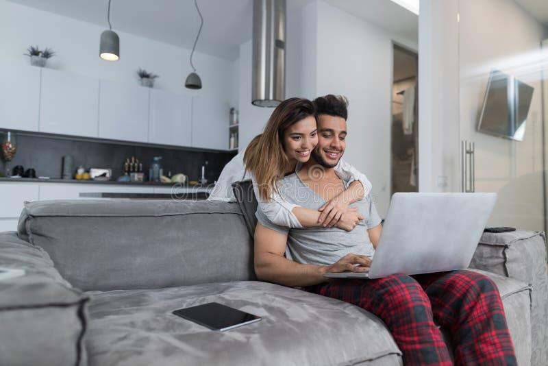 夫妇用途便携式计算机一起在客厅,愉快的微笑的妇女拥抱的人坐长沙发,青年人 免版税图库摄影