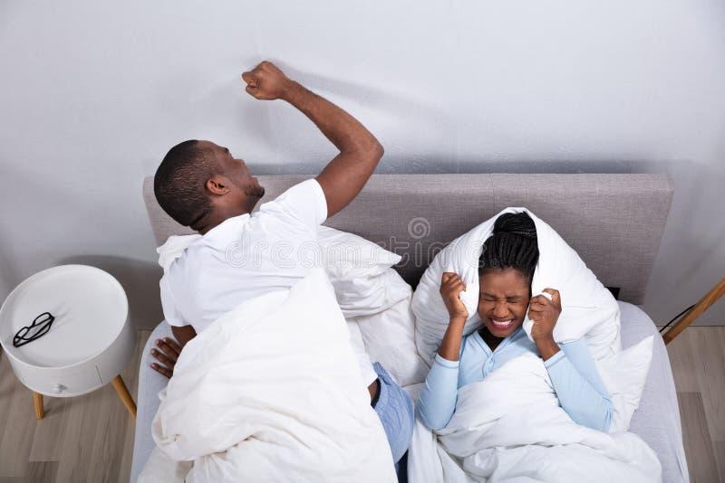 夫妇由在床上的噪声打扰 免版税库存图片