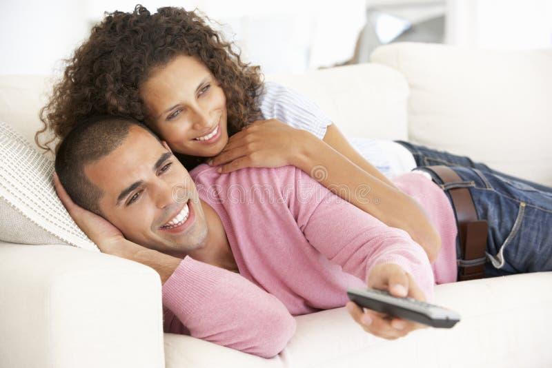 夫妇电视注意的年轻人 免版税图库摄影