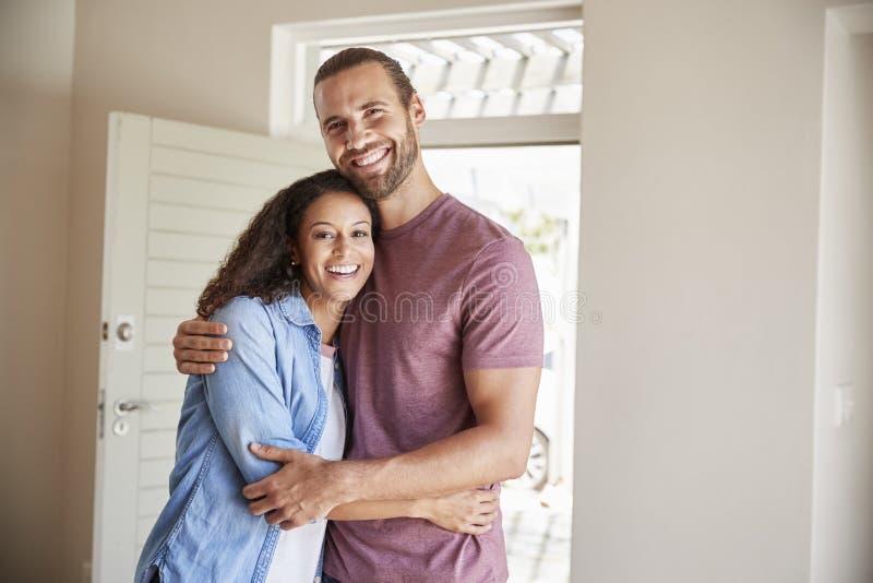 夫妇画象由开放前门的在新的家休息室  免版税图库摄影