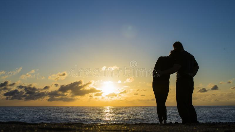 夫妇的后面看法现出轮廓在海滩的拥抱的和观看的太阳 免版税库存照片