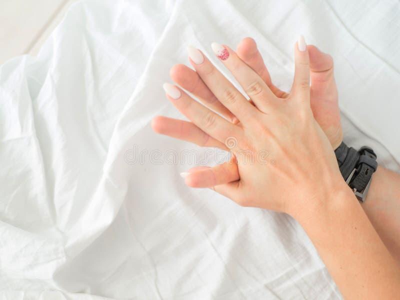 夫妇的手的关闭在床做爱热的性 免版税库存照片
