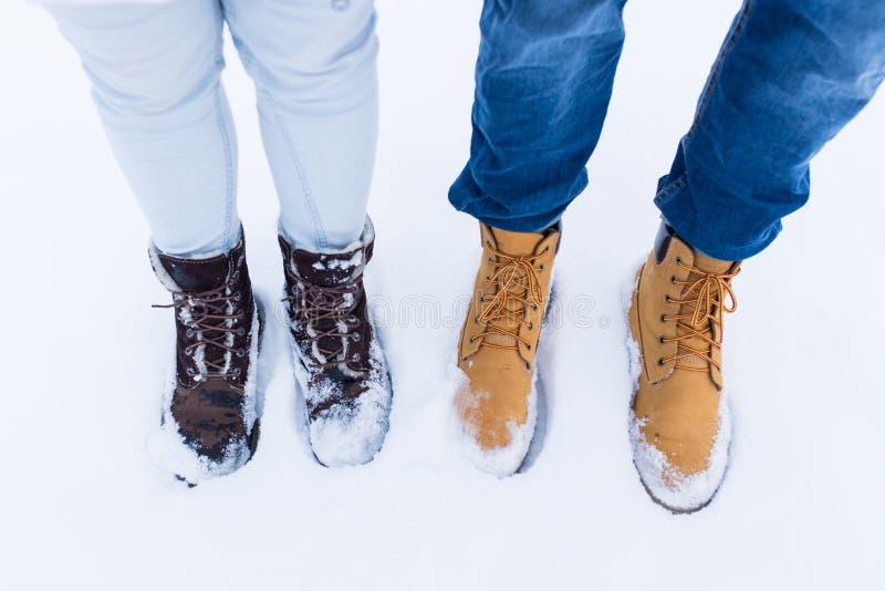 夫妇的腿和脚在爱的在雪的时髦的鞋子 免版税库存图片