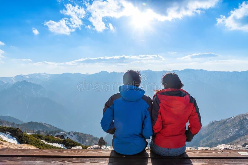夫妇看登上Tsubakuro达克风景在日落 酷寒北风日本阿尔卑斯Chubu-Sangaku公园的山脉 免版税图库摄影