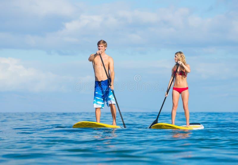 夫妇站立用浆划在夏威夷 库存图片