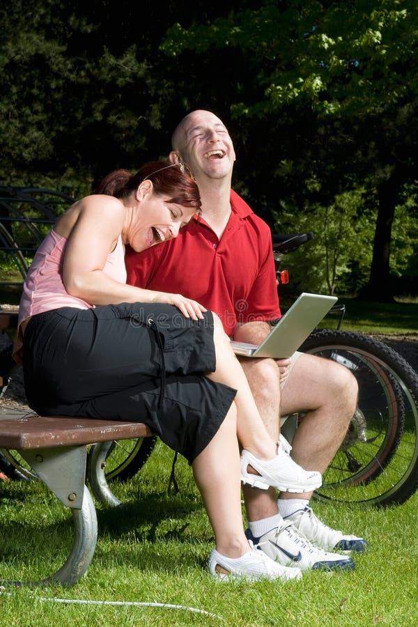 夫妇笑的公园坐的垂直 免版税库存图片