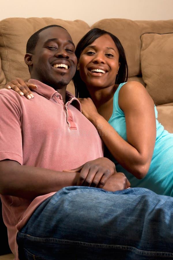 夫妇笑的坐的沙发垂直 免版税图库摄影