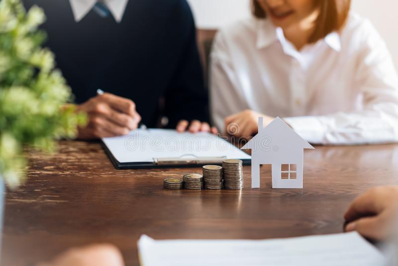 夫妇签合同买从经纪的一个房子 堆积金钱和式样房子的硬币安置在桌 免版税库存图片