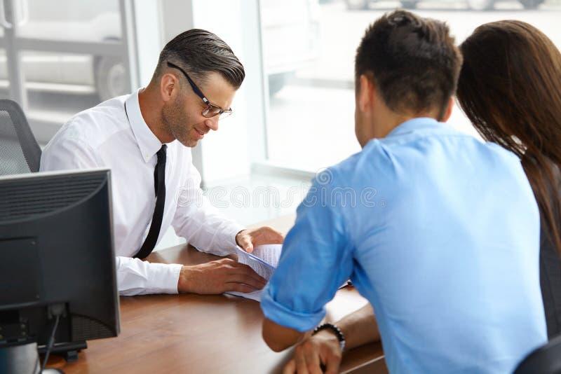 夫妇签署的推销员合同 汽车陈列室 免版税库存照片